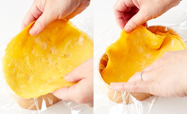 お弁当箱に広げたラップの上に薄焼き卵をのせようとしている写真/ラップの上から薄焼き卵を入れてお弁当箱に広げている写真