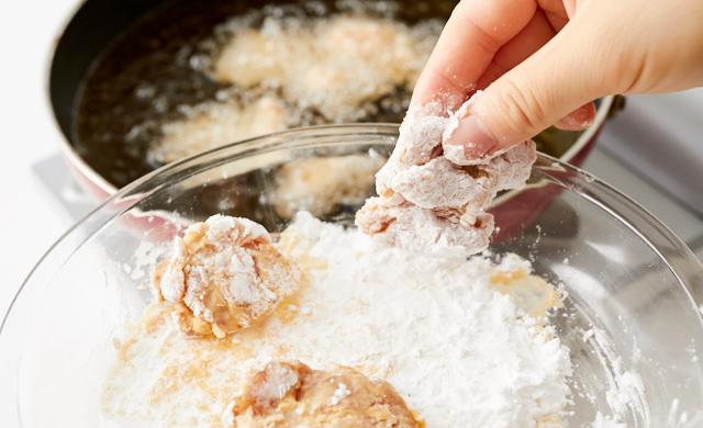 片栗粉を付けた鶏もも肉を揚げ油の中に入れている写真