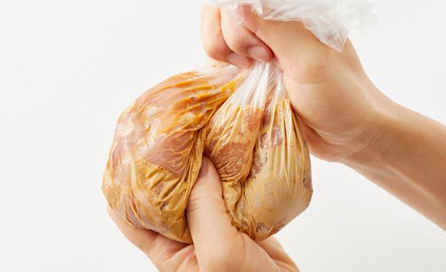 ポリ袋に入れた鶏もも肉、【A】の調味料をもんでいる写真