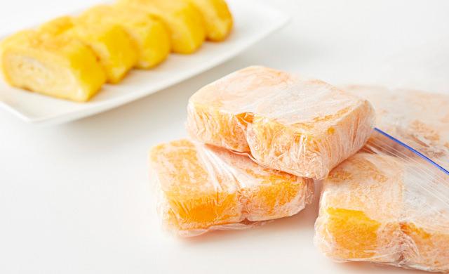 冷凍した卵焼きが保存袋から出ている、奥に食べやすく切った卵焼きの皿盛りの写真