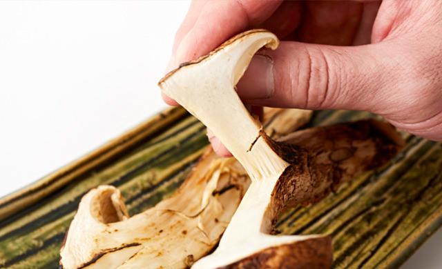 焼き松茸を割いている写真