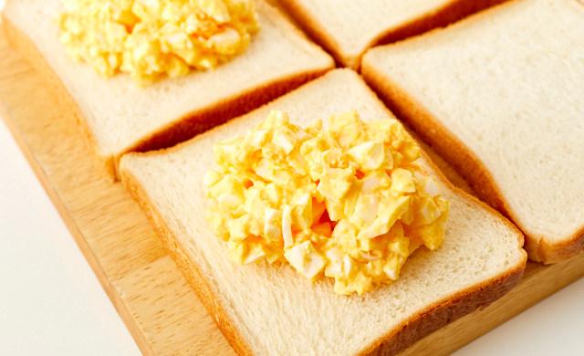 食パンに卵サラダをのせている写真