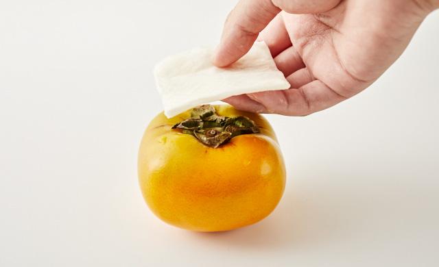 柿にペーパータオルを被せている写真