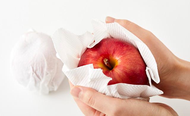 りんごを1個ずつペーパータオルに包んでいる写真