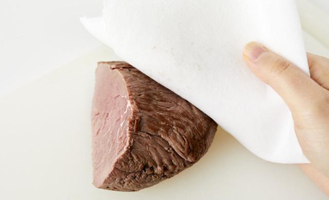 切り分けたローストビーフの表面をペーパータオルで拭いている写真