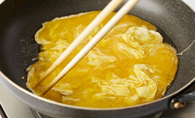 卵液を菜箸で混ぜている写真