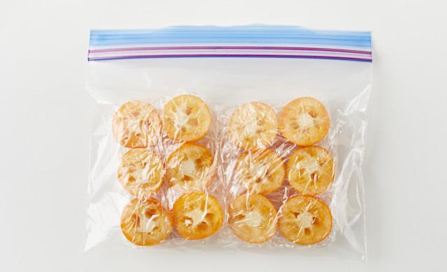 ラップで包んだきんかんを冷凍用保存袋に入れている写真