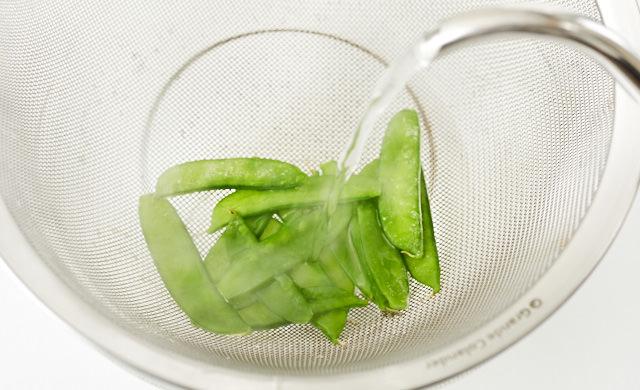 冷凍した絹さやに熱湯をかけている写真
