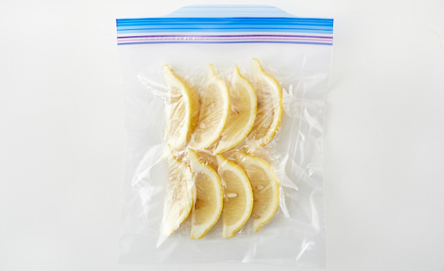 ラップで包んだくし形切りのレモンが冷凍用保存袋に入っている写真
