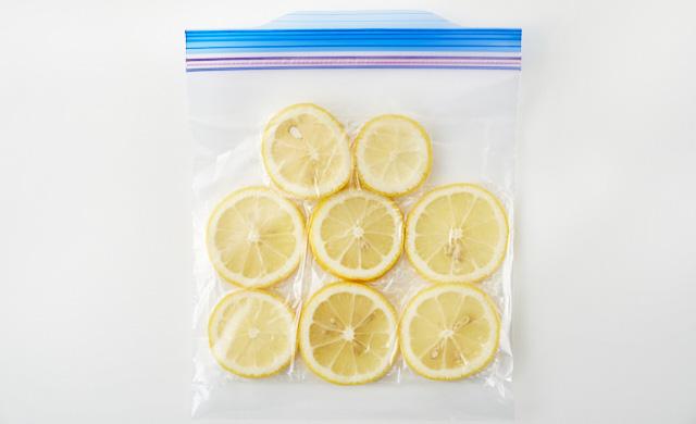 ラップで包んだ輪切りレモンが冷凍用保存袋に入っている写真