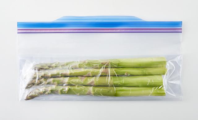 ラップで包んだアスパラが冷凍用保存袋に入っている写真