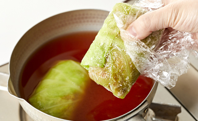 冷凍ロールキャベツを鍋に加えている写真