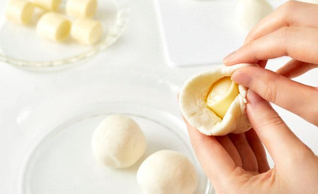 生地でチーズを包んでいる写真