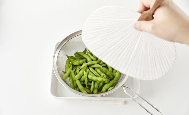 枝豆をうちわで扇いでいる写真