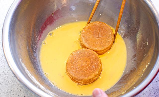 卵液に今川焼を浸している様子