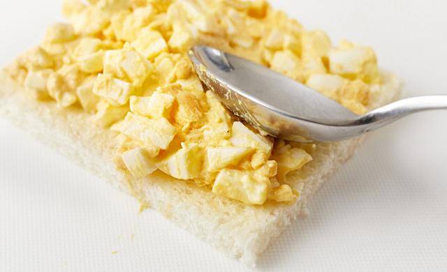 卵サラダをパンに塗っている写真