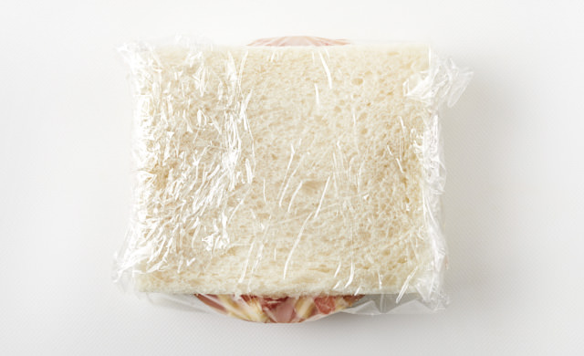 サンドイッチをラップで包んでいる写真