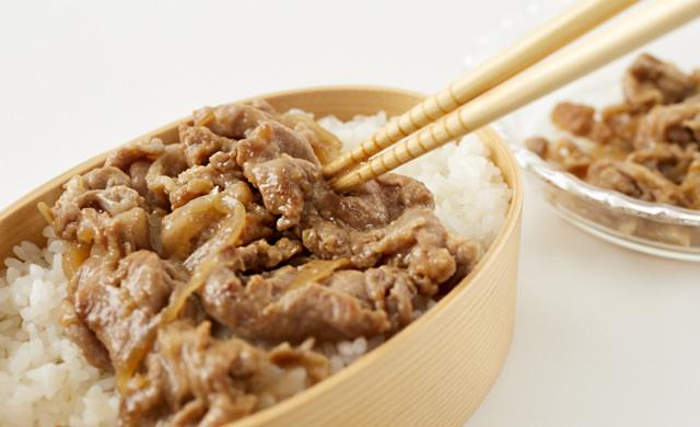 弁当に生姜焼きを詰めている写真