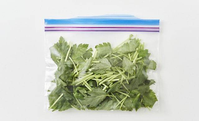 三つ葉を冷凍用保存袋に入れている写真