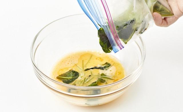 卵液に三つ葉を加えている写真