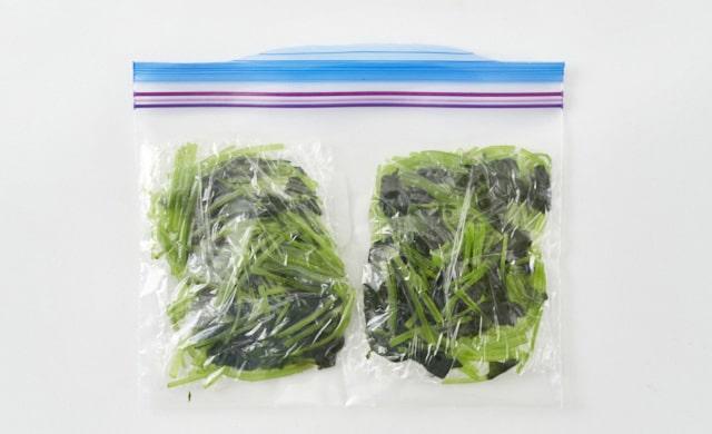 ゆでた三つ葉を冷凍用保存袋に入れている写真