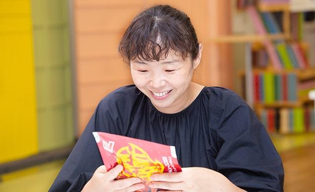 『旨辛チキン』のパッケージを見る金子さんの写真