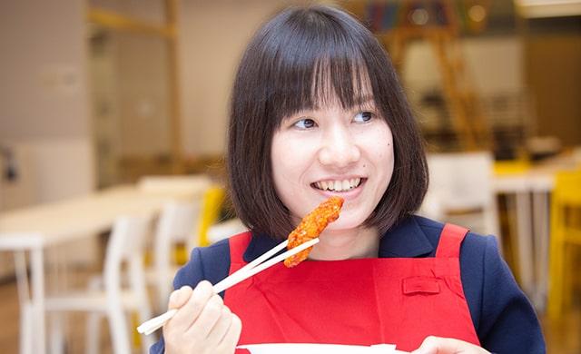 旨辛チキンを食べるニチレイフーズ中澤さん