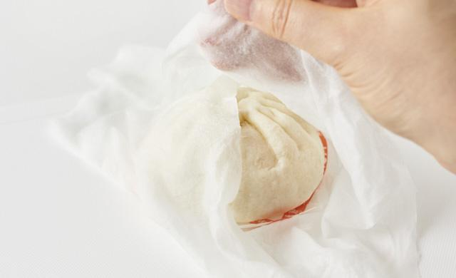 冷凍肉まんを濡らしたペーパータオルで包んでいる写真