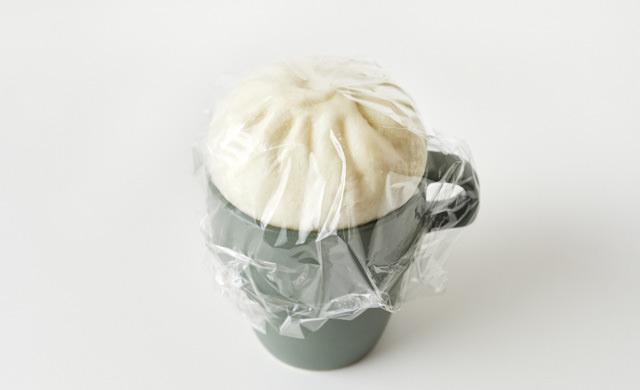 冷凍肉まんをマグカップにのせてラップをかけた写真