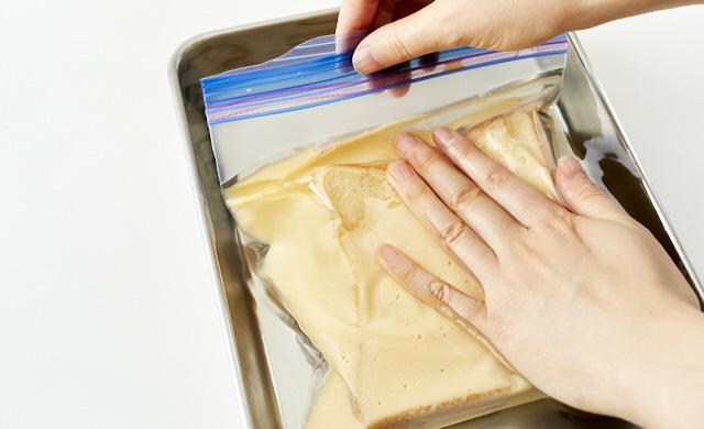 冷凍用保存袋の空気を抜いているところ写真