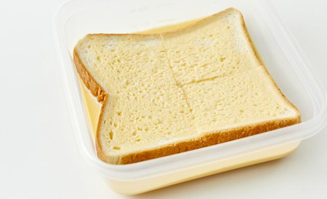 凍ったままのパンを卵液に浸している写真