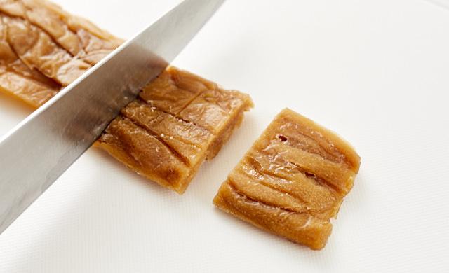 凍ったかんぴょうの甘辛煮をカットしている写真
