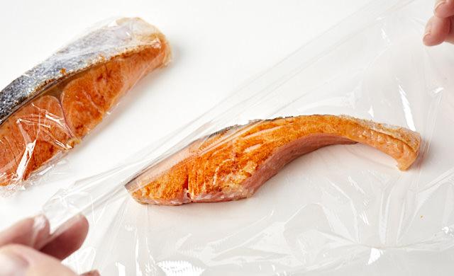 焼き魚をラップで包んでいる写真