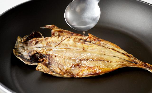 凍ったアジの開きの焼き魚に水を振りかけている写真