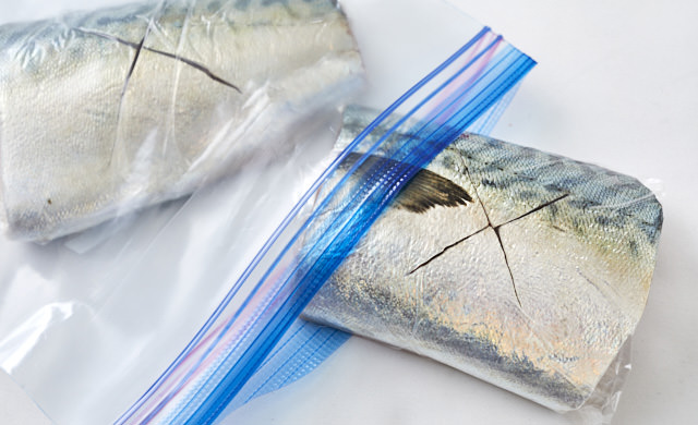 冷凍用保存袋にラップで包んだサバを入れている写真