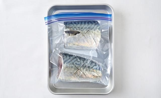 冷凍用保存袋に入ったサバをバットに並べている写真