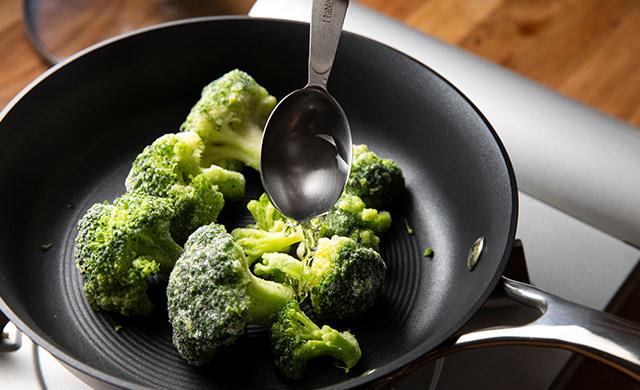 冷凍ブロッコリーをフライパンに入れ水を加える写真