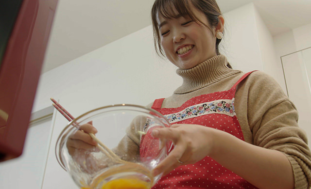 卵焼きを作っている娘さんの写真