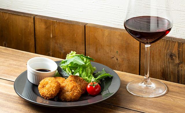 『お肉たっぷりジューシーメンチカツ』と赤ワインの写真