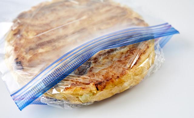 ラップで包んだお好み焼きを冷凍用保存袋に入れている写真