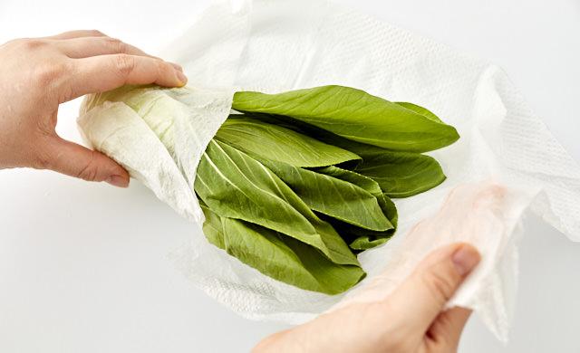 チンゲン菜をペーパータオルで包んでいる写真