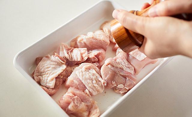 鶏もも肉に塩・こしょうをかけている写真